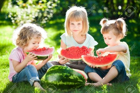 12235383-Group-of-happy-children-eating-watermelon-outdoors-in-spring-park-Stock-Photo