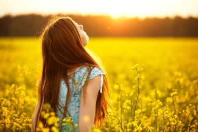 Young woman enjoying sunlight in canola field