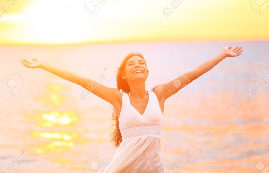 19387053-Freedom-woman-happy-and-free-open-arms-on-beach-at-sunny-sunset-Beautiful-joyful-elated-woman-lookin-Stock-Photo