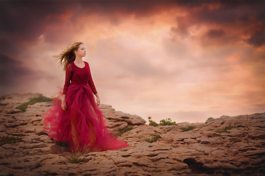 portrait-of-a-girl-in-a-red-dress-standing-on-the-rocks-of-a-mountain-at-Mallorca-beach-by-Willie-Kers
