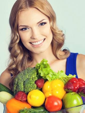 42478528-portrait-of-cheerful-smiling-young-lovely-woman-with-healthy-vegetarian-raw-food-against-blue-backgr