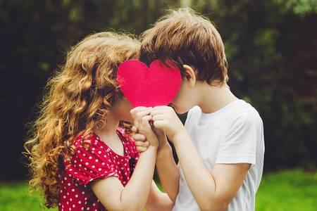 51001164-cute-children-holding-red-heart-shape-in-summer-park-valentines-day-background-.jpg